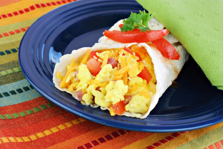 Delicious breakfast egg, tomato, cheese and pepper burrito.